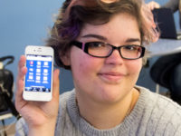 Liberal arts major Chani Pickett, 19, of Urbandale, holds up her phone with the DMACC app.