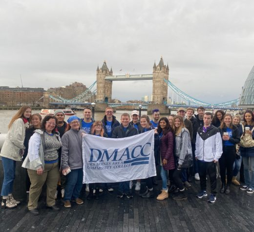 The 2020 Study Abroad group holds a DMACC banner in front of Tower Bridge.